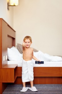 happy kid watching tv in hotel room after bathing